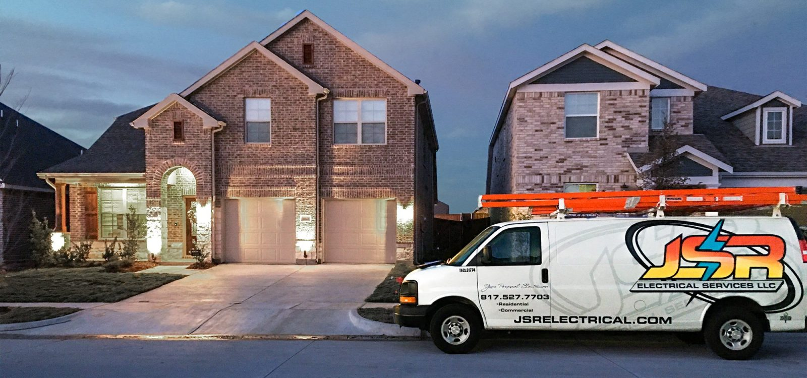 Outdoor lighting installation and landscape lights with a JSR electrical service van sitting in front of a home.