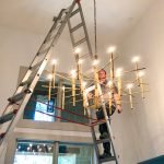 A JSR electrician with a very large heavy light fixture.