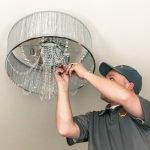 A JSR Electrician installing a ceiling lighting fixture.