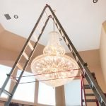 Crystal Heavy Chandelier installed on a home ceiling, with a tall ladder in front.