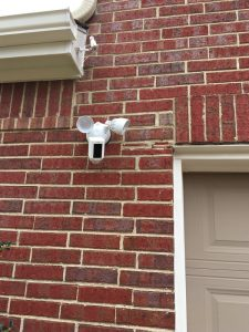 Outdoor motion sensor security cameras installed on a home exterior brick wall.