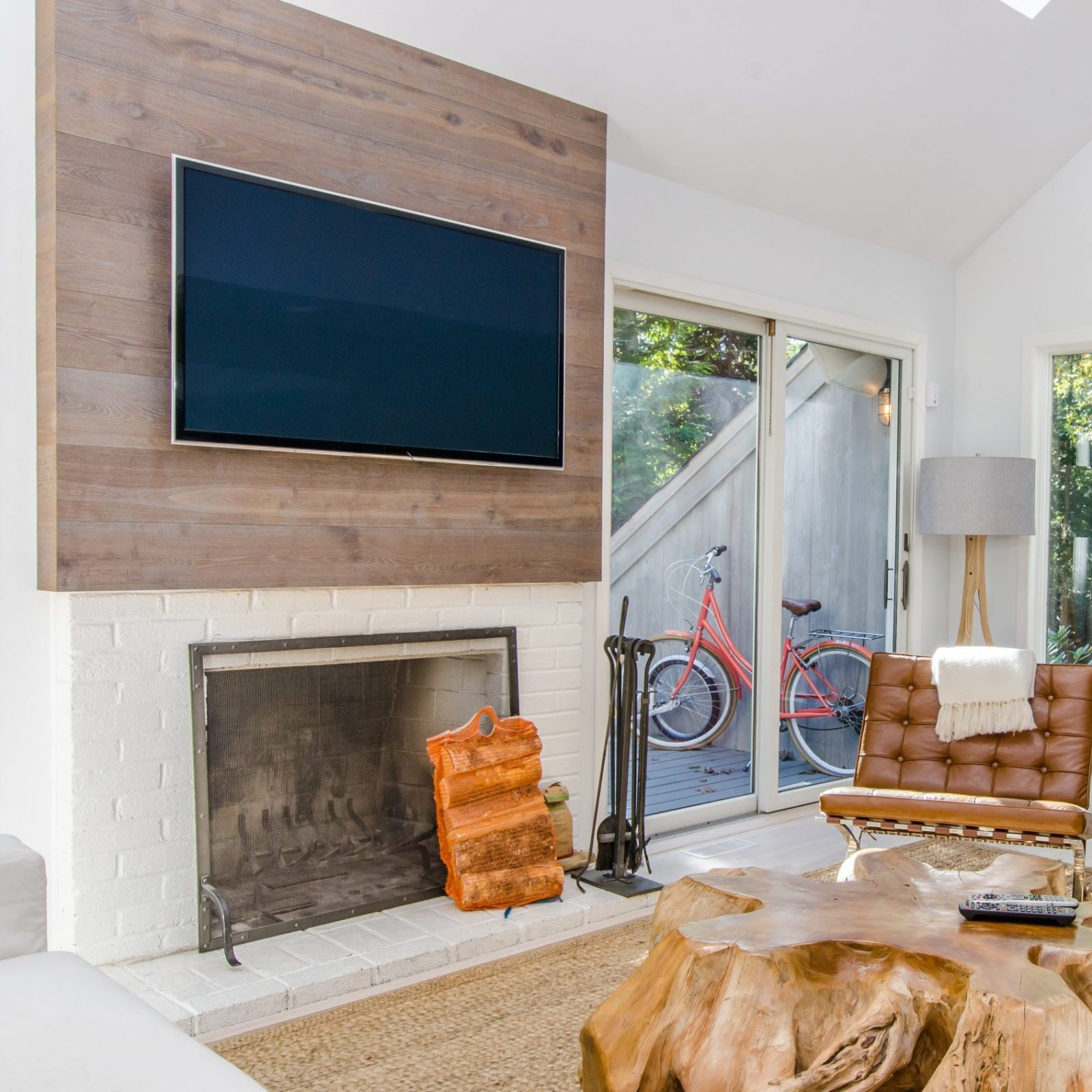 A Flat Panel Television mounted on a wood wall above a fireplace in a living room.