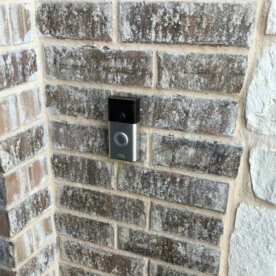 Ring security doorbell installed on a brick wall next to a home entrance.