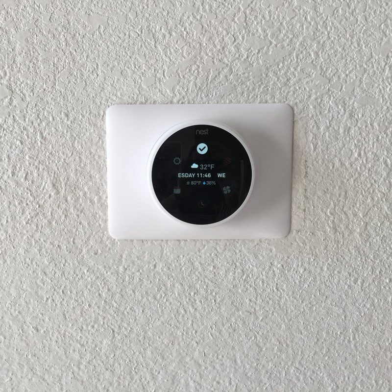 Nest Indoor Thermostat installed on a home wall.