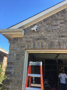 Ring outdoor security camera installed on a brick wall.
