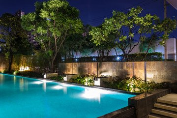 Outdoor lights on a fence surrounding a pool. This is a home backyard at night.